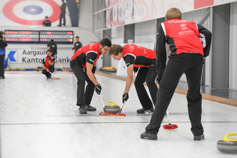 Zwei Mitglieder eines Curlingteams wischen den Spielstein in Richtung des Hauses