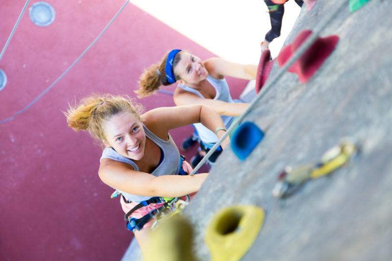 Zwei Jugendliche klettern eine Kletterwand hoch