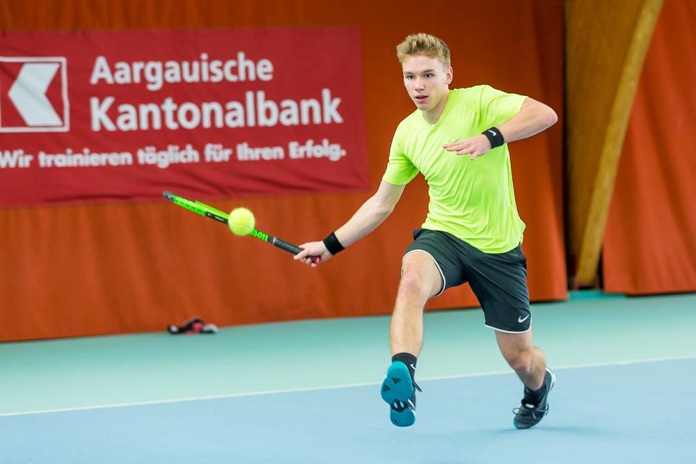 Ein junger Tennisspieler schlägt eine Vorhand aus vollem Lauf