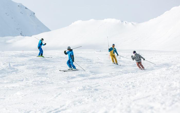 Eine Gruppe von vier Skifahrern fährt hintereinander über die Piste
