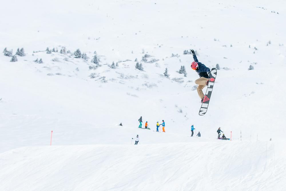 Ein junger Snowboarder springt über eine Schanze