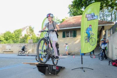 Ein Mädchen fährt mit einem Mountainbike über eine Rampe
