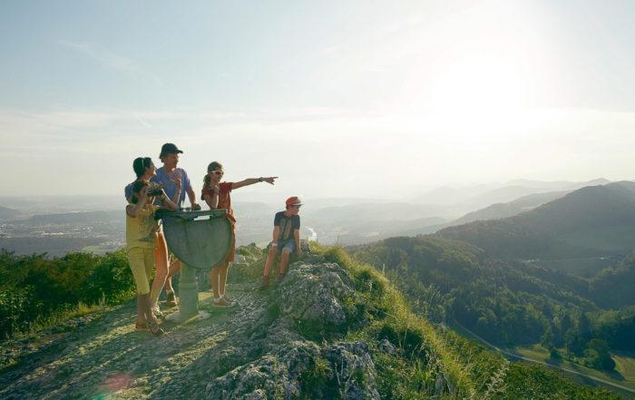 Eine Familie geniesst den Ausblick auf einem Hügel