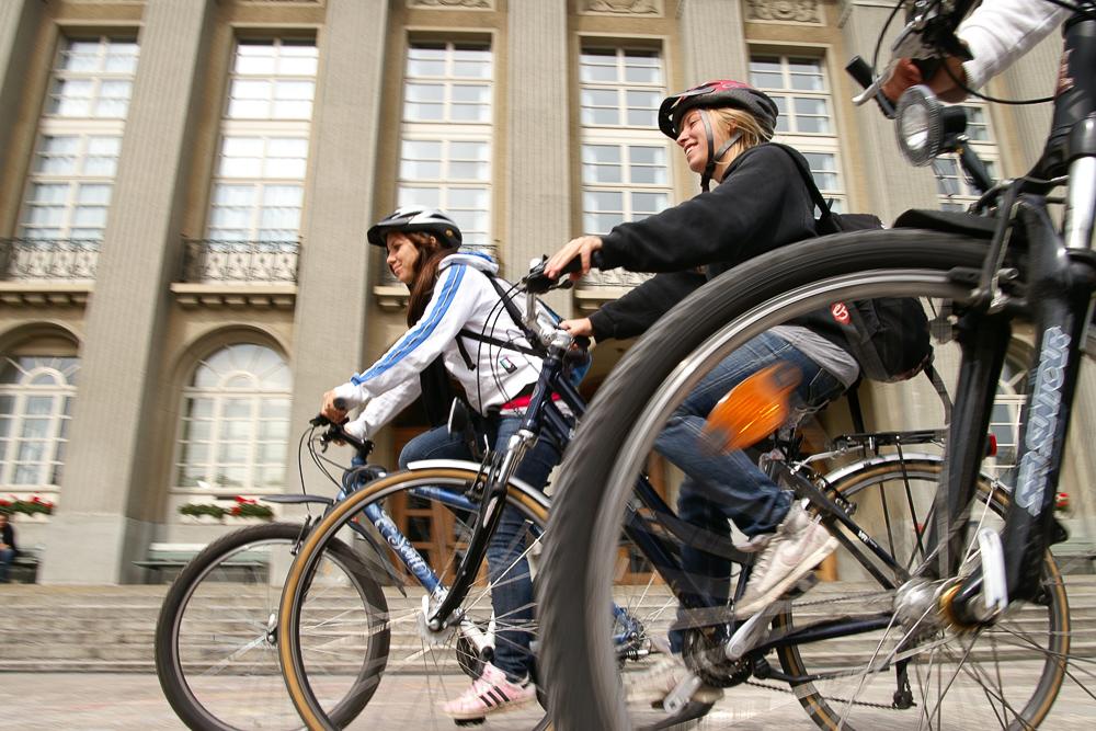 Drei Schülerinnen fahren mit ihrem Velo zur Schule
