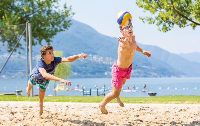 Zwei Jungs spielen Beachvolleyball und hechten nach einem Ball