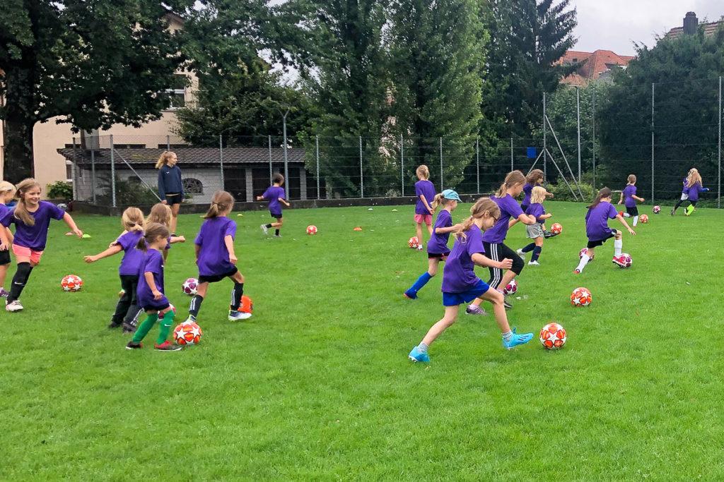 Junge Mädchen spielen Fussball in einer Gruppe