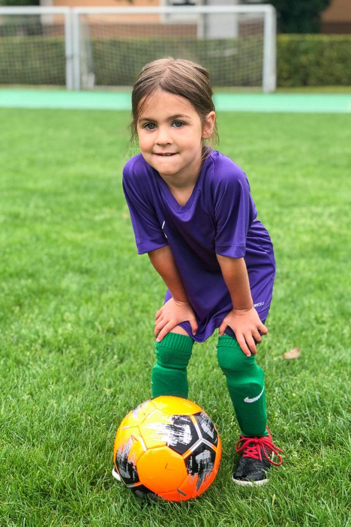 Eine junge Fussballerin posiert mit dem Ball