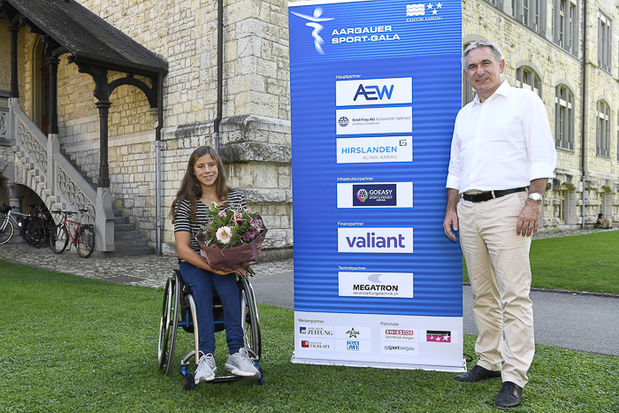Sportminister Alex Hürzeler überreicht Para-Schwimmerin Nora Meister ihr Geschenk