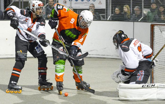 Zwei Inline Hockeyspieler im Direktduell vor dem Tor