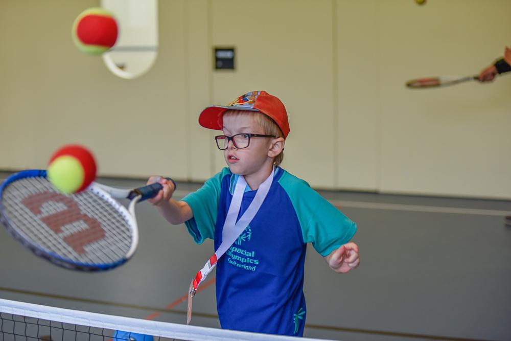 Ein Kind mit einer Beeinträchtigung beim Tennisspielen