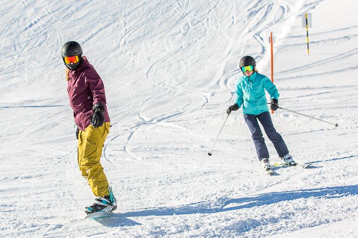 Ein Ski- und ein Sknoboardfahrer sind auf der Piste unterwegs