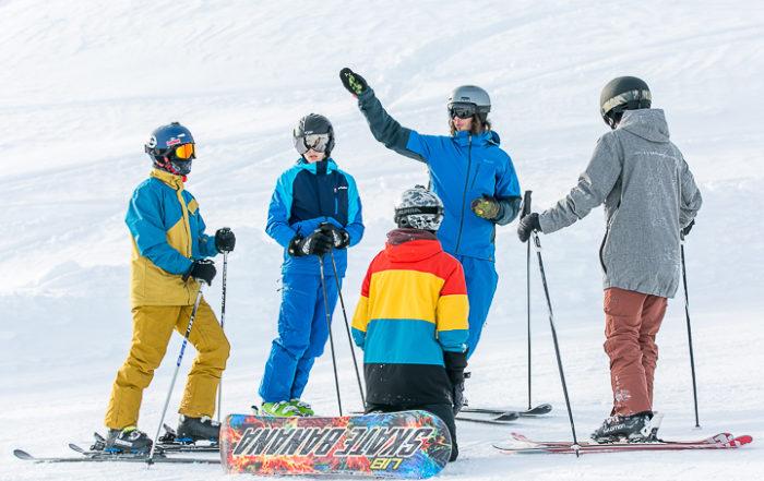 Ein Leiter erklärt vier Jugendlichen Ski- und Snowboardfahrern eine Übung im Jugendsportcamp des Kantons Aargau