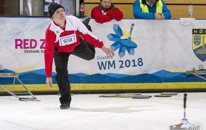 Ein Eisstock-Sportler schiesst seinen Eistock
