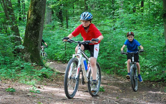 Zwei Jungs fahren auf dem Mountainbike durch den Wald