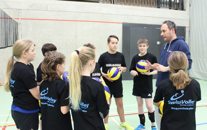 Volleyball-Nachwuchsspieler erhalten Instruktionen von ihrem Trainer